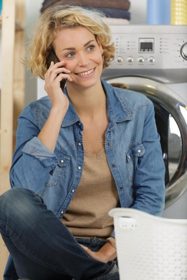 Happy woman on phone calling someone near washing machine royalty free stock image