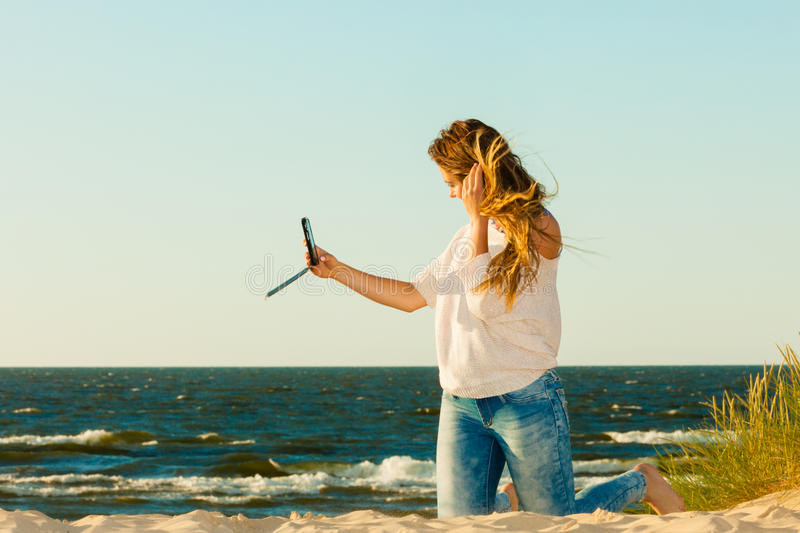 Happy woman with phone taking selfie photo. Fun with photography. Young smiling woman with mobile phone taking selfie picture photo. Happy cute gril with long royalty free stock image