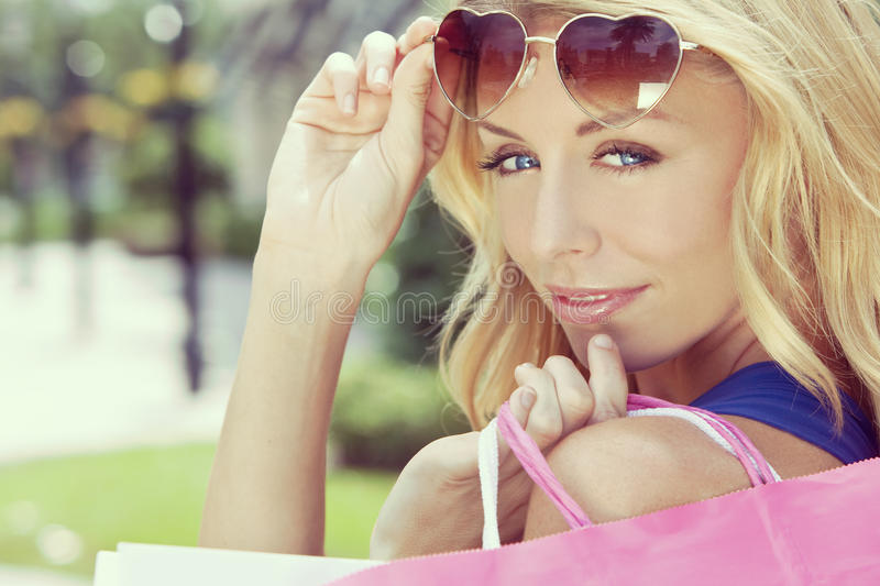 Happy Woman With Pink and White Shopping Bags. Instagram style happy and fashionable woman with colorful pink and white shopping bags and wearing heart shaped royalty free stock photography