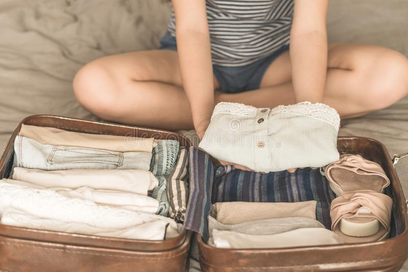 Happy woman planning a travel preparing a suitcase royalty free stock images