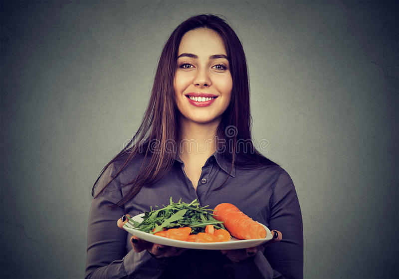 Happy woman with plate of vegetables royalty free stock images