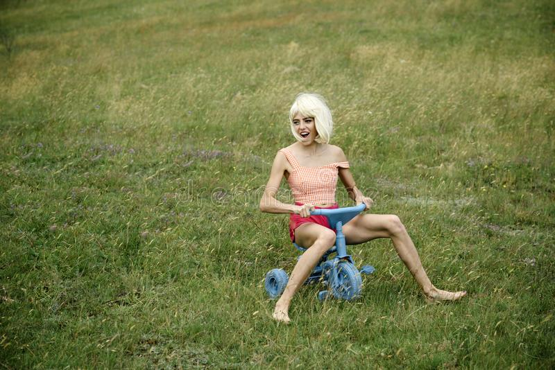 Happy woman play on toy bicycle in summer. royalty free stock images