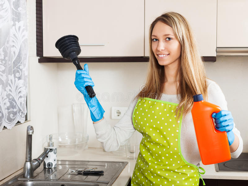 Happy woman with plunger and detergent in kitchen stock images