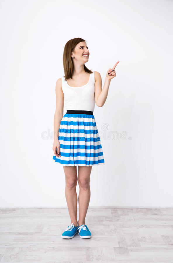 Happy woman pointing up and looking away royalty free stock photo