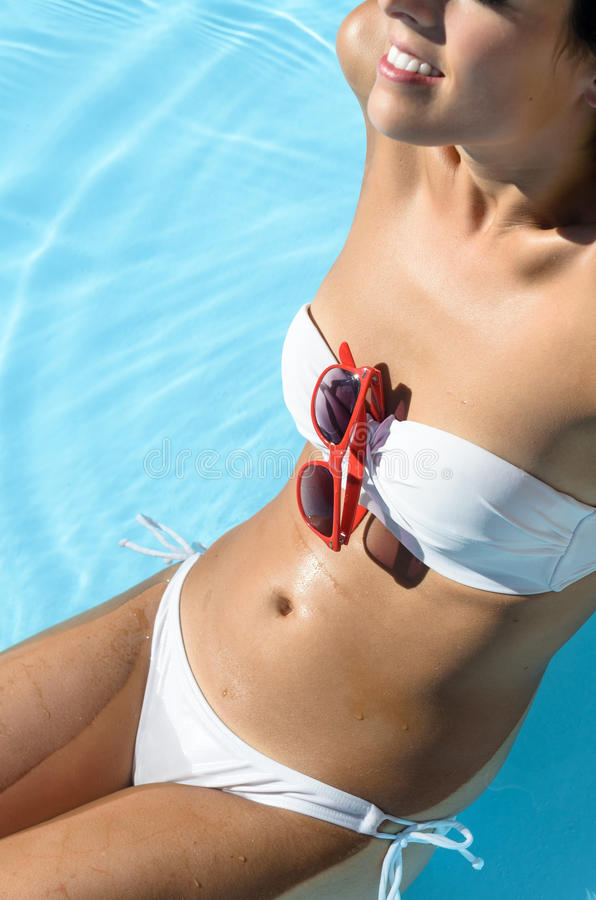 Happy woman in pool sunbathing stock images