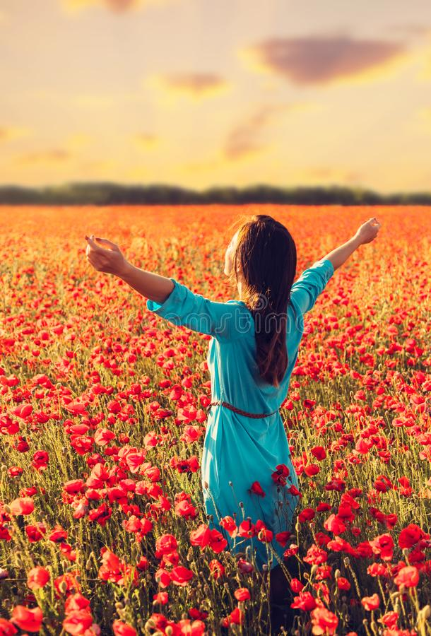 Happy woman in poppies meadow. stock images