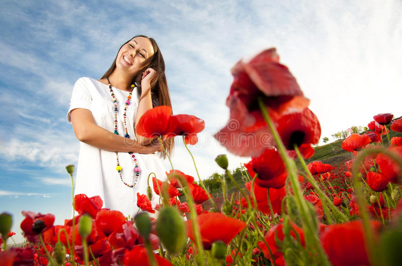 Happy woman in poppy field royalty free stock image