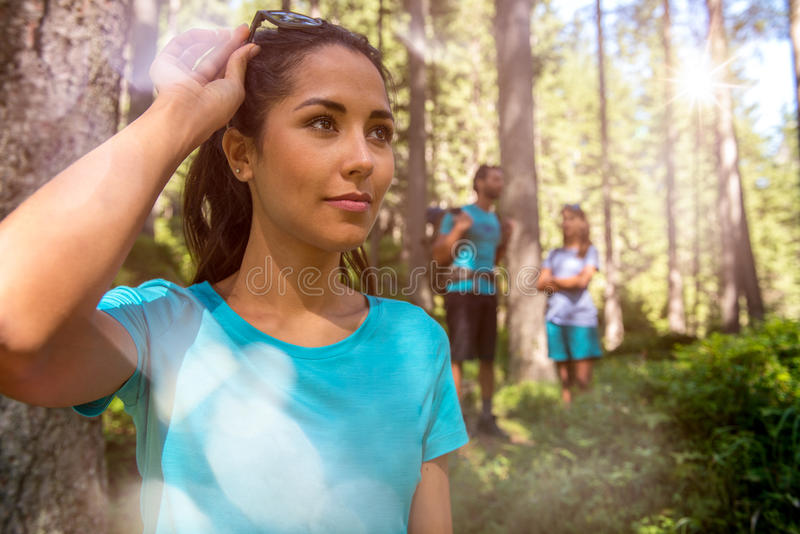 Happy woman portrait with man and girl hiking trail path in forest woods during sunny day.Group of friends people summer stock image