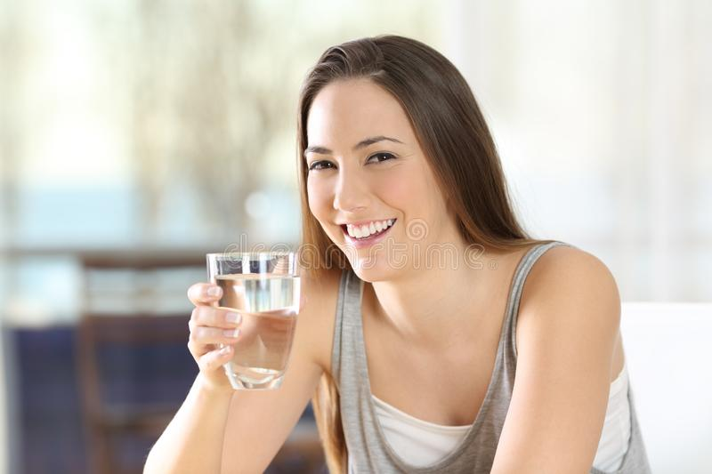 Happy woman posing holding a glass of water royalty free stock photos