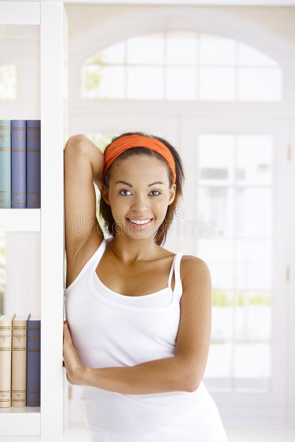 Happy woman posing at home. Happy afro woman posing at home, standing by book shelf, smiling at camera stock photography