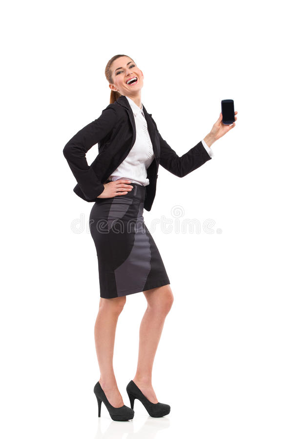 Happy woman posing with smart phone. Smiling elegance woman showing cell phone. Full length studio shot isolated on white stock image