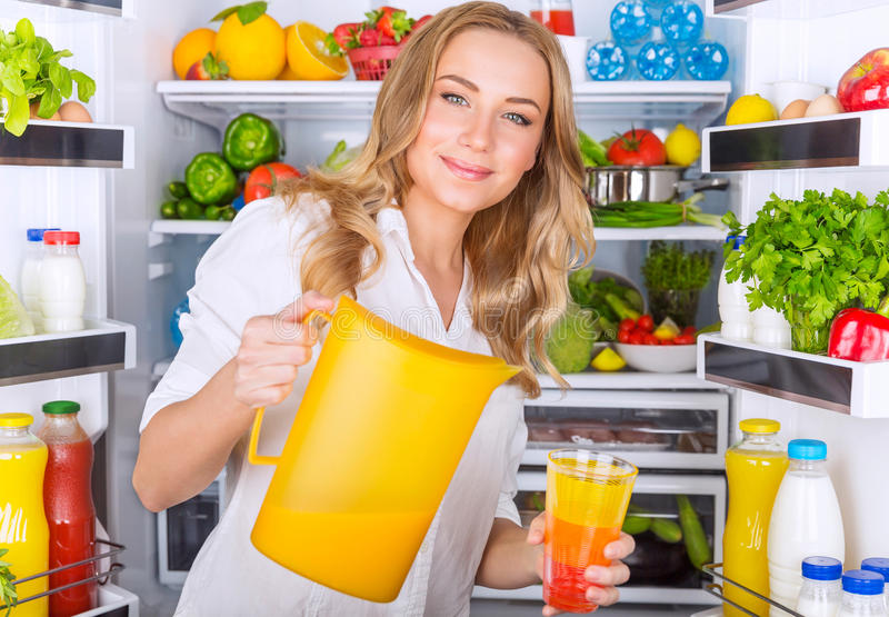 Happy woman pouring juice. Happy woman standing near open refrigerator full of fresh fruits and vegetables and pouring juice in glass, healthy eating concept royalty free stock image