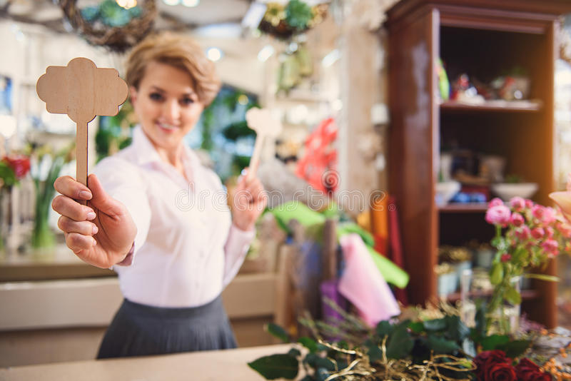 Happy woman presenting wood objects in flower shop stock image