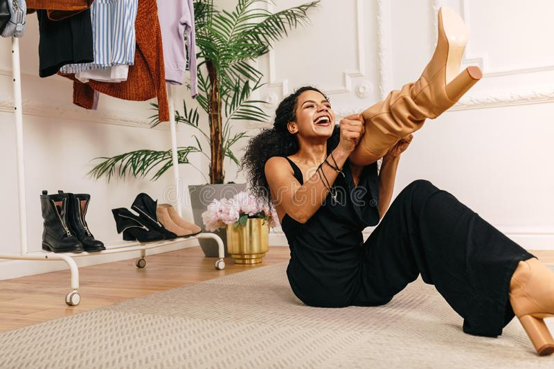 Happy woman pull on knee-high boot on a leg stock photography
