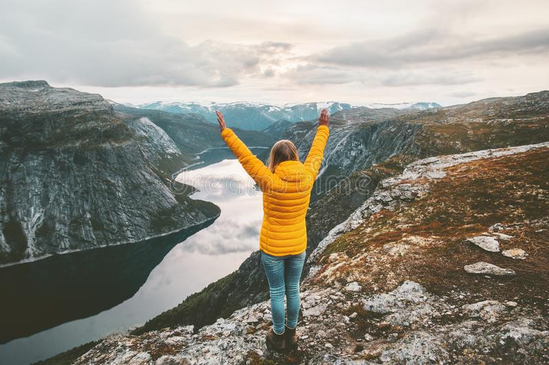 Happy woman raised hands on mountain summit. Traveling alone adventure lifestyle journey vacations aerial lake landscape success wellness emotions stock image