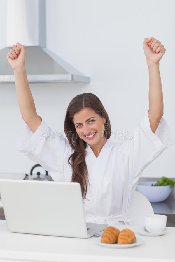 Happy woman raising arms while using a laptop