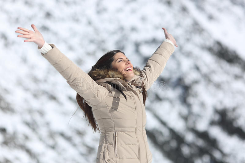 Happy woman raising arms on winter holidays. With a snowy mountain in the background royalty free stock photo