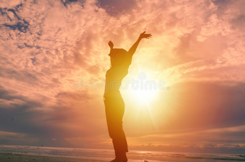 Happy woman raising hands up and beautiful sunrise in background royalty free stock photos