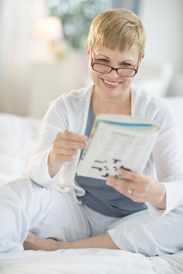 Download Happy Woman Reading Book On Bed Stock Photo - Image: 33119922