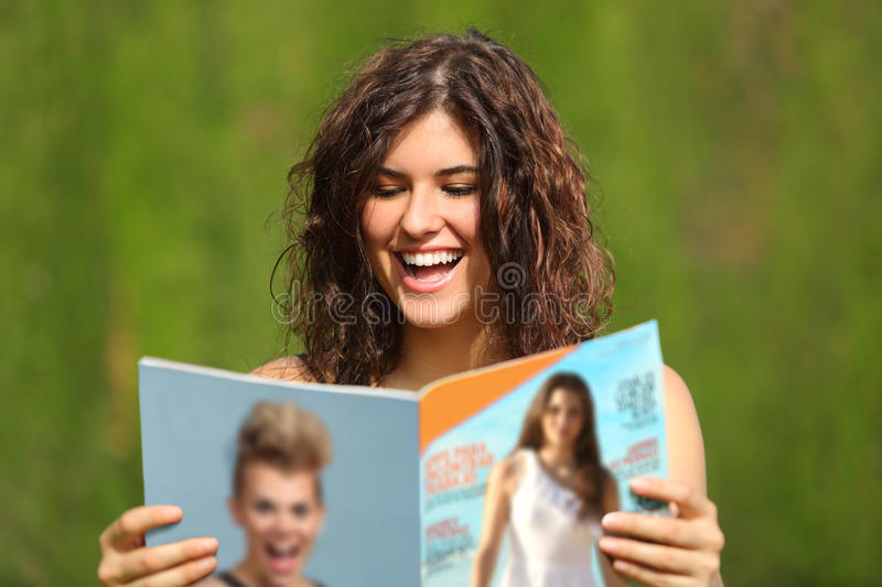 Happy woman reading a magazine stock images