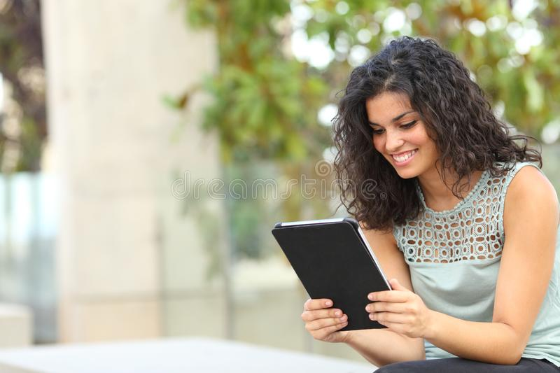 Happy woman reading online content in a tablet or ebook. Sitting on a bench in a park stock photo