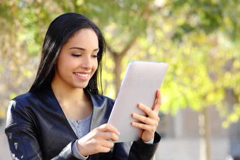 Happy woman reading a tablet reader in a park. With a green background