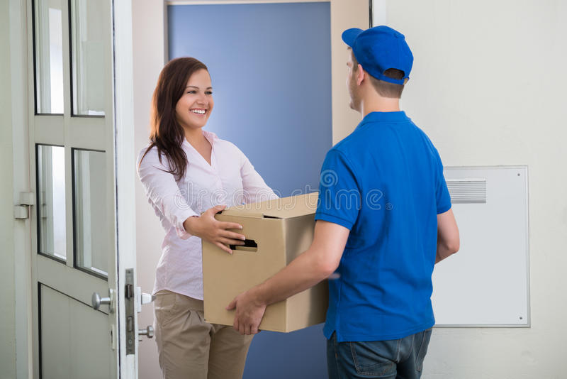 Delivery Man Gives Package To Woman. Happy Woman Receiving Package From Delivery Man At The Doorway stock image
