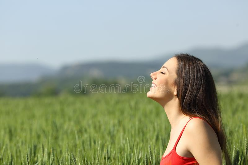 Happy woman in red breathing fresh air in a field stock images
