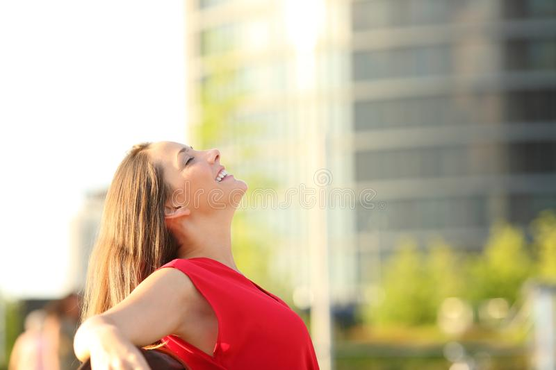 Happy woman in red breathing fresh air in the street royalty free stock photos