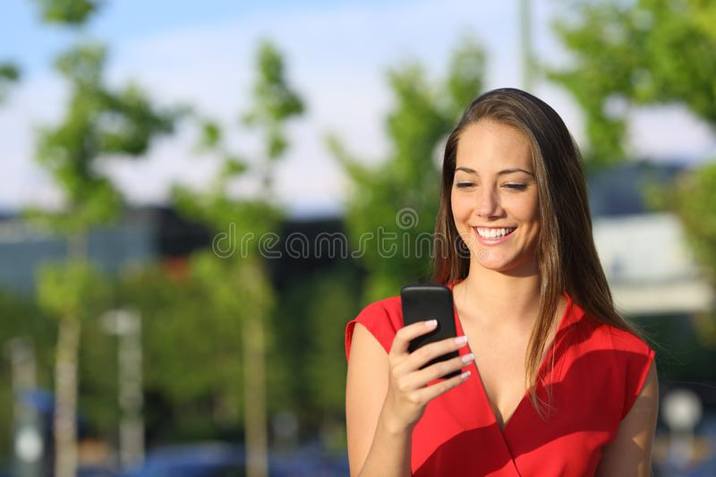 Happy woman in red checking phone text in the street stock image