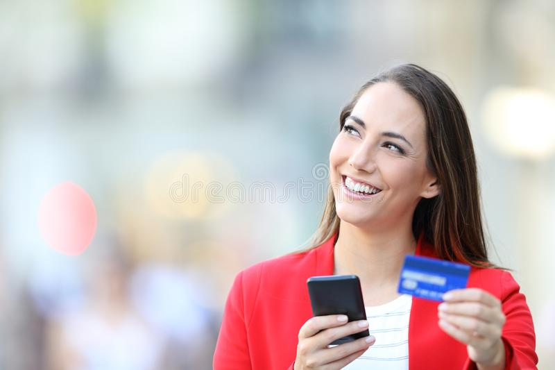Happy woman holding credit card and phone thinking royalty free stock image
