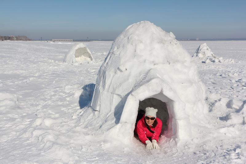 Happy woman in a red jacket lying in an igloo. On a snowy glade royalty free stock photo