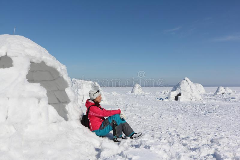 Happy woman in a red jacket sitting at the entrance in an igloo. On a snowy glade royalty free stock photo