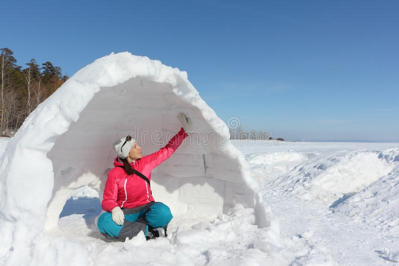 Happy woman in a red jacket sitting in unfinished an igloo. On a snowy glade, Siberia, Russia stock photos