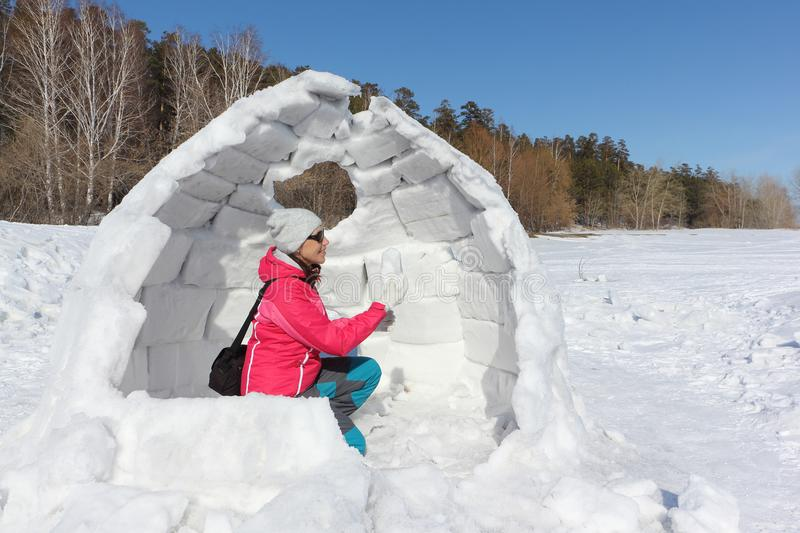 Happy woman in a red jacket sitting in unfinished an igloo. On a snowy glade, Siberia, Russia stock photography