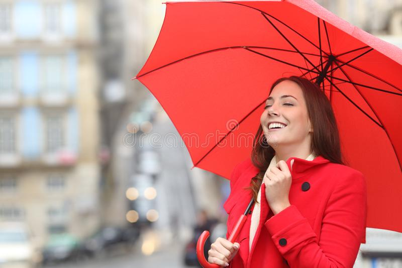 Happy woman in red keeping warm in a rainy winter day. In the street royalty free stock photography