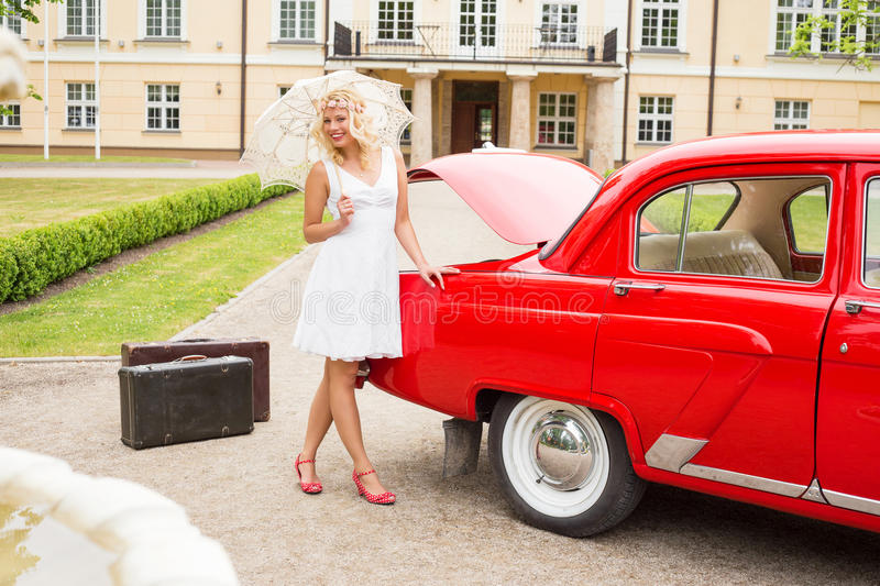 Happy woman with red retro car stock images