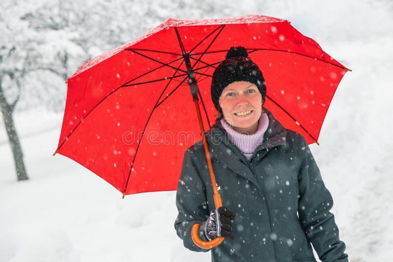 Happy woman with red umbrella enjoying winter snow stock photo