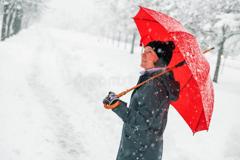 Happy woman with red umbrella enjoying winter snow stock photography