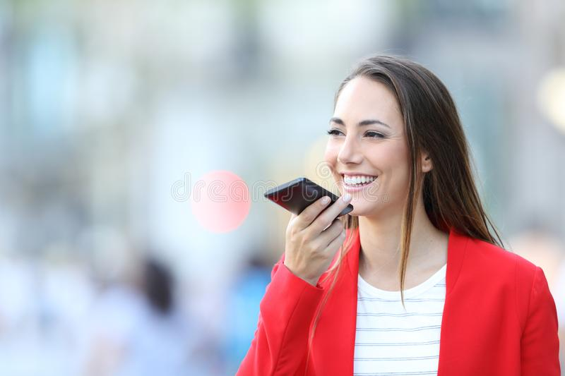 Happy woman in red using voice recognition on phone royalty free stock image