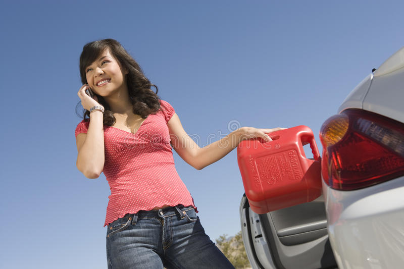 Happy Woman Refueling Her Car While Talking On Cell Phone stock photography