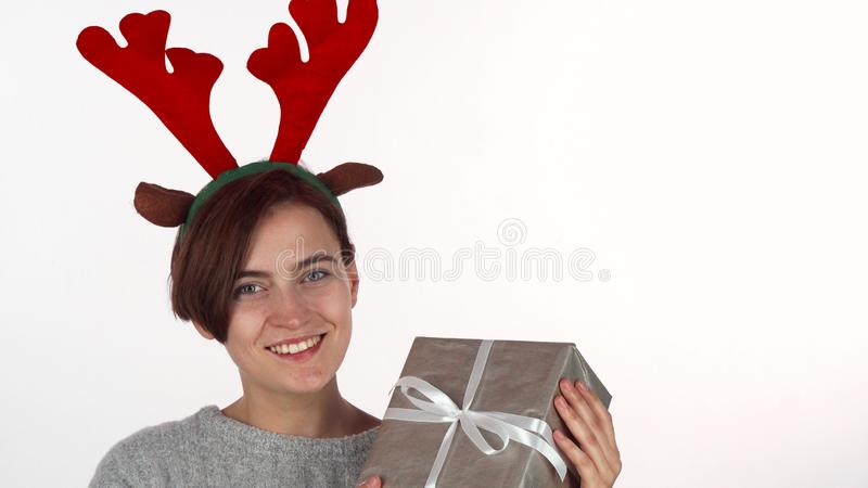 Happy woman in reindeer antlers headband looking at her Christmas present. Beautiful young woman celebrating New Year, holding gift box, smiling to the camera royalty free stock images