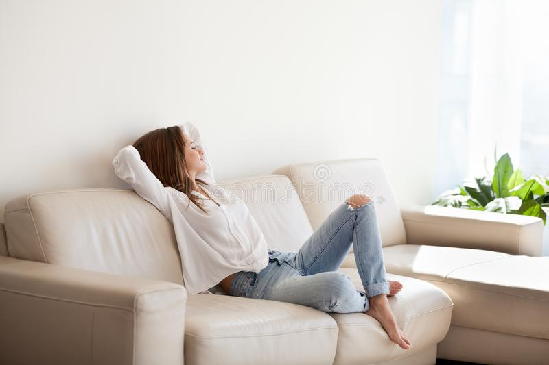 Happy woman relaxing on comfortable sofa enjoying weekend at hom royalty free stock image