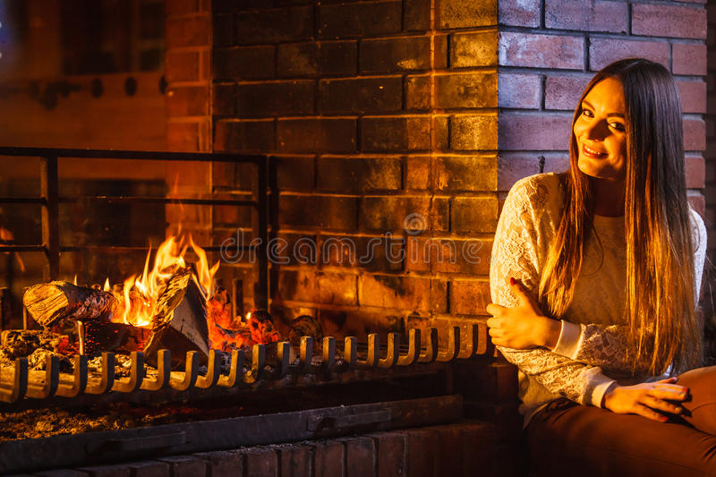 Happy woman relaxing at fireplace. Winter home. Joyful happy woman relaxing resting at fireplace. Young girl heating warming up. Winter at home royalty free stock photo