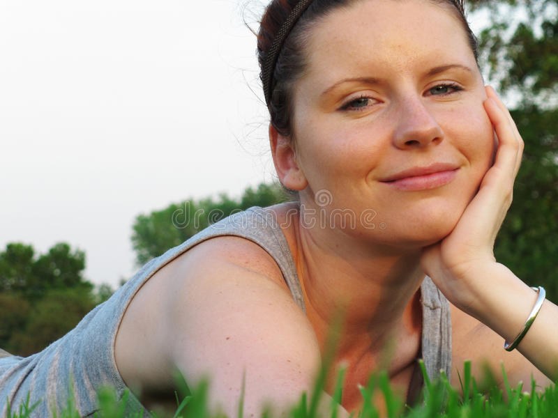 Happy woman relaxing on green grass in the garden.