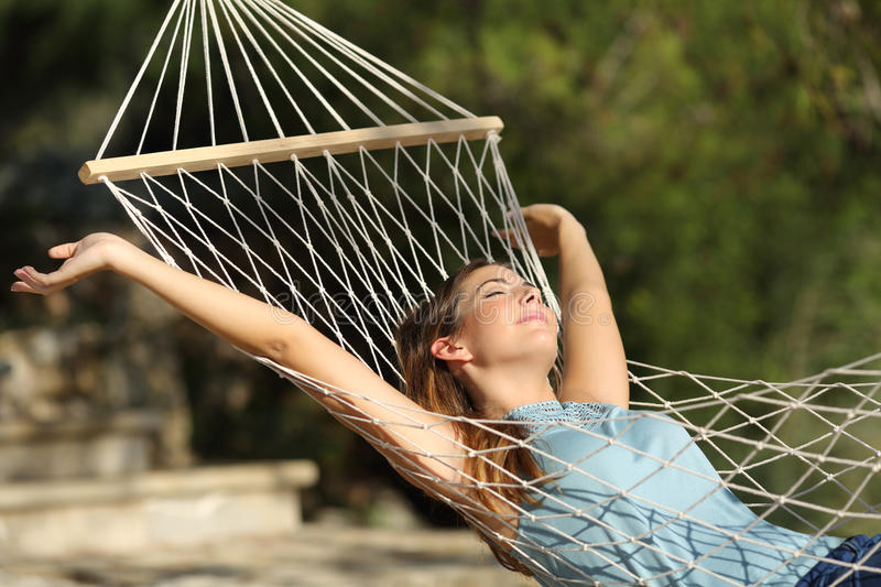 Happy woman relaxing on a hammock on holidays and raising arms. In the mountain royalty free stock photos