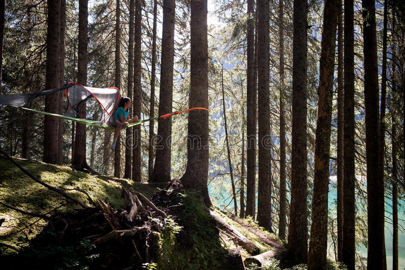 Happy woman relaxing in hanging tent camping in lake forest woods during sunny day.Group of friends people summer. Adventure journey in mountain nature outdoors royalty free stock photos