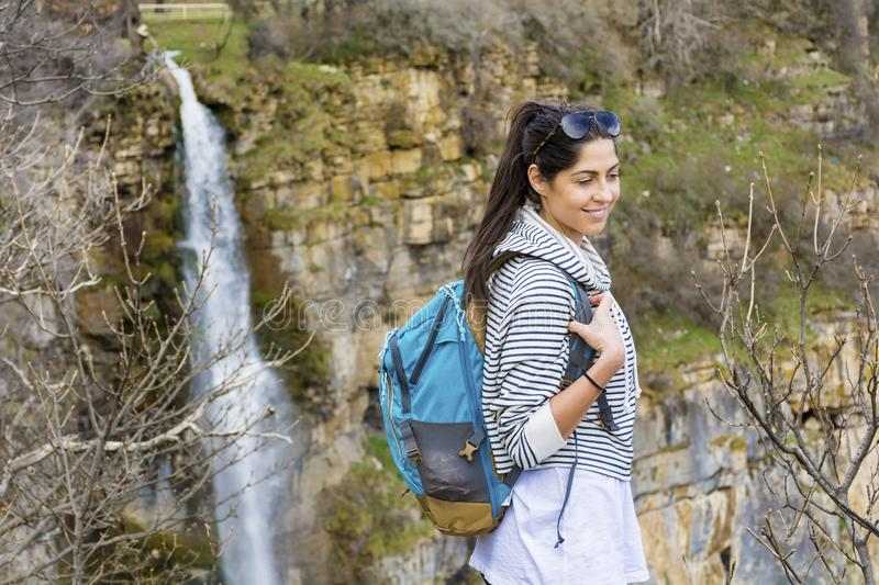 Hiker Woman on a Waterfall Background. Happy woman relaxing in a high mountain and Enjoying the Lush Waterfall View from above .Adventure Concept royalty free stock photo
