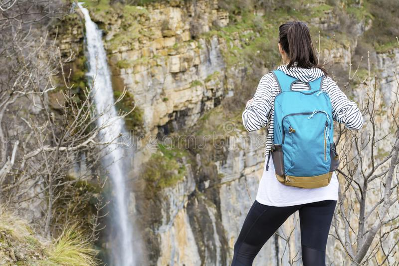 Hiker Woman Looking Waterfall in the Mountain. Happy woman relaxing in a high mountain and Enjoying the Lush Waterfall View from above .Adventure Concept royalty free stock photography