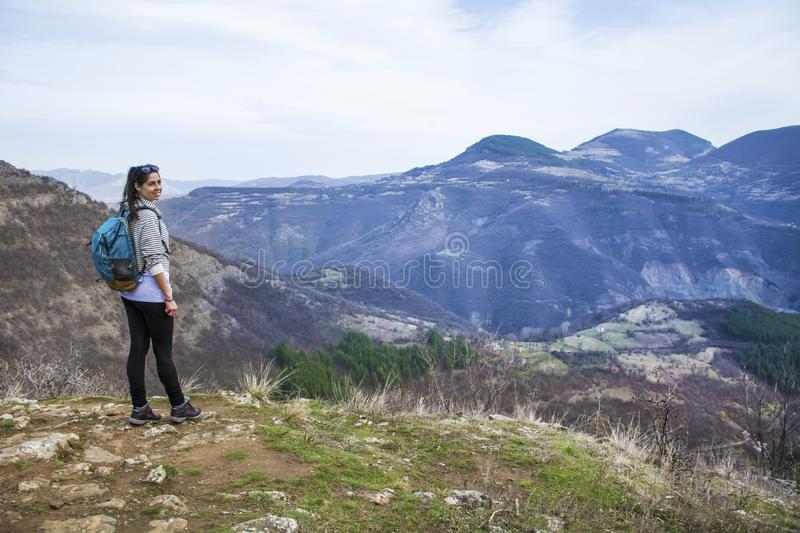 Hiker Woman Looking the Mountain View. Happy woman relaxing in a high mountain and Enjoying the Panoramic View from above .Adventure Concept royalty free stock photography